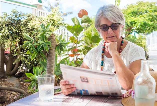 One retired pretty senior woman sitting and looking at the newspaper in the garden. drinking a glass of water. tropical plants and blue sky