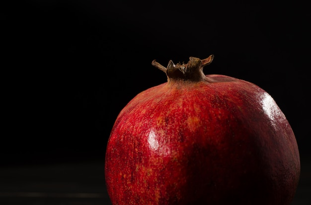 One ripe pomegranate on a black wooden background