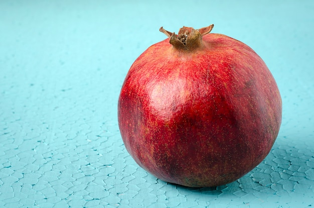 One ripe pomegranate on blue background