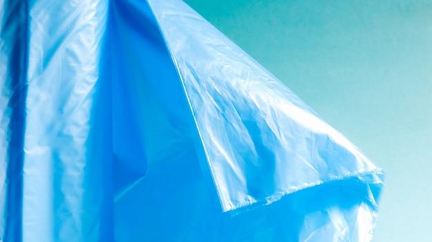 青の背景に青のプラスチック製ゴミ袋の1つのロール。ごみを入れるように設計され、家庭で使用され、さまざまなごみ容器に入れられるバッグ。