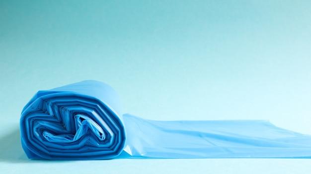 青の背景に青のプラスチック製ゴミ袋の1つのロール。ごみを入れるように設計され、家庭で使用され、さまざまなごみ容器に入れられるバッグ。スペースをコピーします。