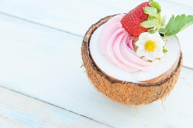 イチゴとクリームチーズの木製のテーブルの上半分のココナッツ