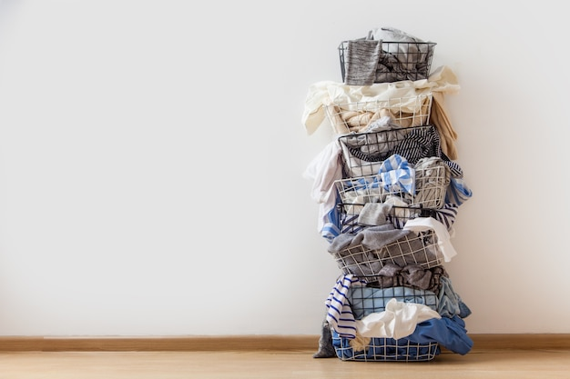 One row of stacked metal laundry basket with full of clothing on white background.