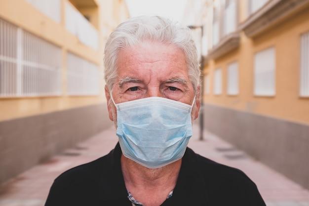 Covid-19 또는 코로나바이러스를 방지하기 위해 마스크를 쓰고 카메라를 보고 있는 슬프고 화난 노인 또는 성숙한 사람 - 검역 및 잠금 상태에서 집에 머물며 카메라를 보고 있습니다.