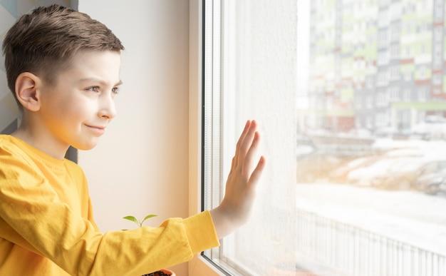 낮 시간에 창 근처에 서있는 슬픈 어린 소년.