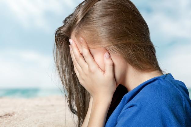 한 슬픈 여자는 벽 근처 바닥에 앉아서 머리를 손에 들고 있다