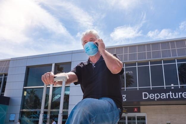 パンデミックで世界中を旅する準備ができている1人の年配の成熟した男性-病気やcovid-19を防ぐために外科的および医療用のマックを身に着けている空港の年金受給者-彼の電話を呼び出して使用する