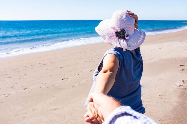 해변에서 모래사장에서 남편의 손을 잡고 걷고 있는 한 노년의 여성 - 여름에 함께 새로운 장소를 발견하고 - 바다에서 휴가를 보내는 연금 수급자