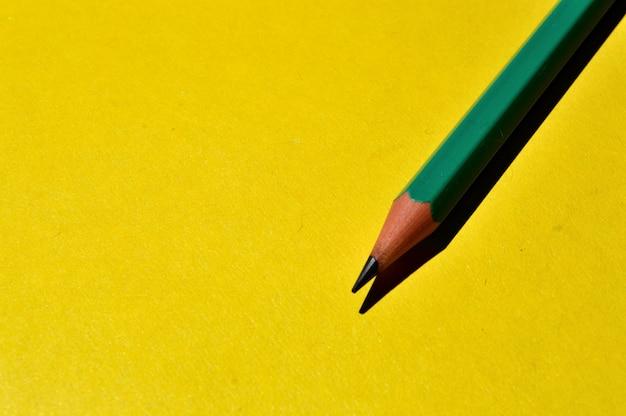 하나의 날카롭게 연필은 노란색 배경에 놓여 있습니다. 확대.
