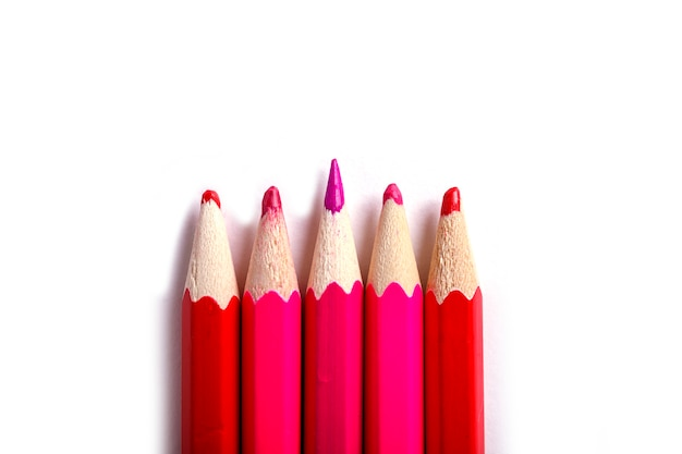 One sharpened pencil standing out from the blunt ones. it's easy to be beautiful if you do nothing concept. red pencils on white.