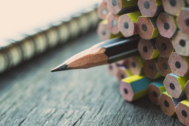 One sharpened pencil standing out from the other new pencil on wood table.
