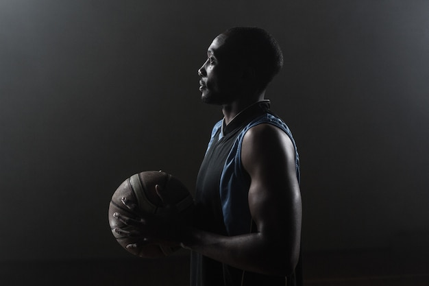 One side of a basketball player holding a basketball