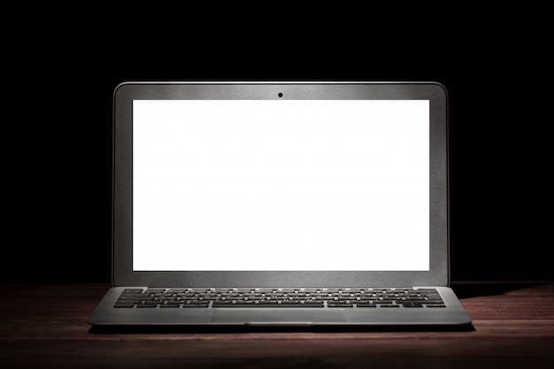 One silver modern laptop with empty white screen on wooden table in a dark room on black background.