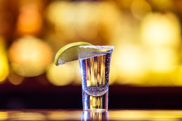 One silver tequila in a glass on bright lights. traditional mexican drink.