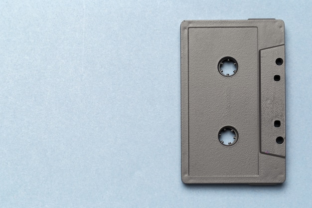 One single retro audio cassette on light grey, top view