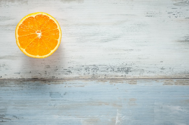 One slice of fresh oranges on painted wooden board