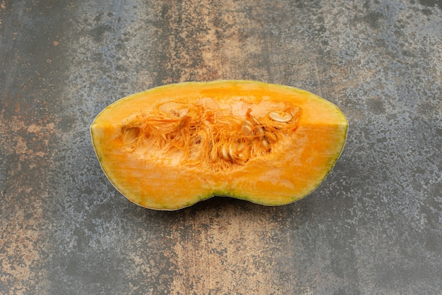 One slice of fresh yellow pumpkin on marble surface