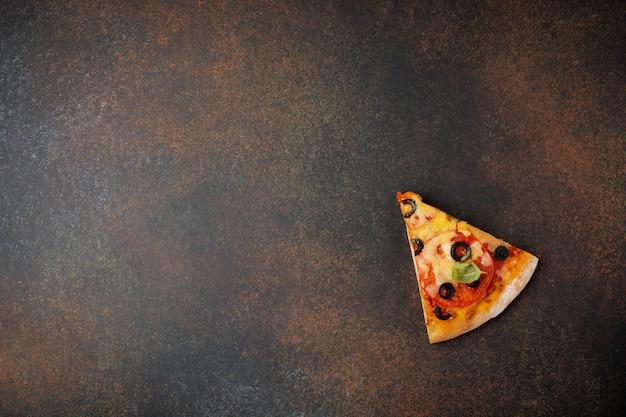 Один кусок пиццы маргарита на темном бетонном фоне