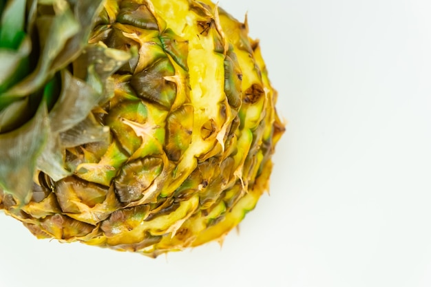 One sliced pineapple on isolated white background, shot from above. top view of ripe fresh pineapple standing on white table