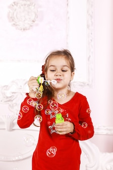 One small girl dressed in red pajamas is playing with bubbles indoors