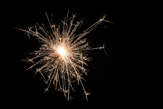 One small new year sparkler on black.
