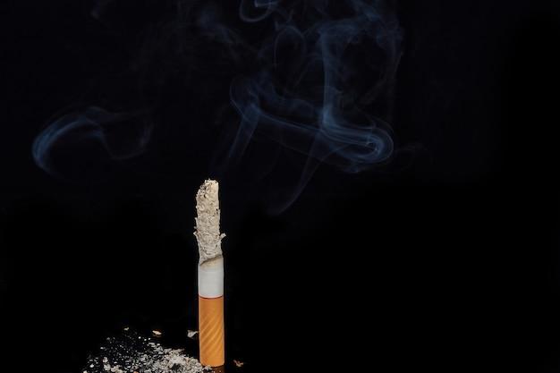 Одна курящая сигарета на черной поверхности