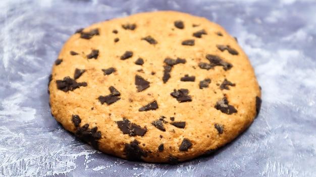 灰色の大理石のキッチンカウンターにある、柔らかく焼きたてのチョコレートチップクッキー。アメリカの伝統的なデザート。おいしいお菓子。休日のための自家製のベーキングコンセプト。料理の背景。