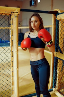 One sportive female mma fighter in boxing gloves poses in a cage in gym.