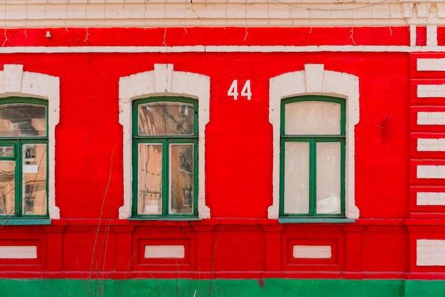 赤いファサードに建物の看板番号44がある1階建ての家。緑の木製窓。街。都市