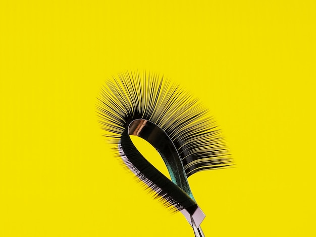 One strip of eyelashes for arc extension on a yellow background.