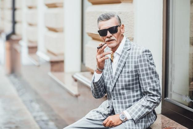 Один стильный старик курит сигарету в сером костюме. крупным планом