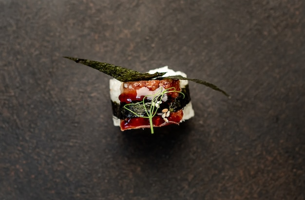 Один суши-ролл на каменном фоне