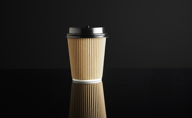 Картонный бумажный стаканчик на вынос, закрытый крышками, изолированными на черном и зеркальными. розничная презентация