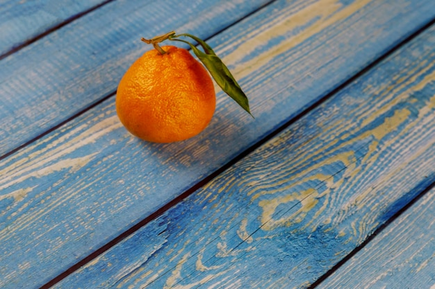 One tangerine with leaf on wooden table