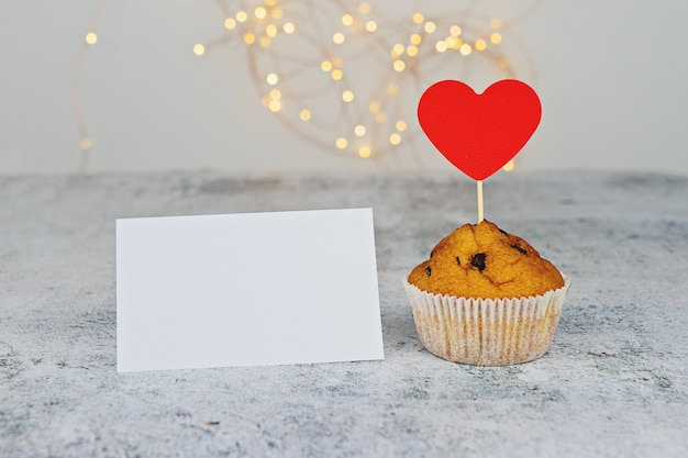 One tasty cupcake with big red hearts and empty valentine card