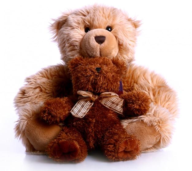 One teddy bear hugs another