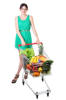 One teen girl in green dress with supermarket trolley full of groceries, shopping cart full of food, isolated over white surface