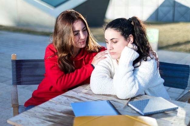 Одна девушка-подросток утешает другого после разрыва