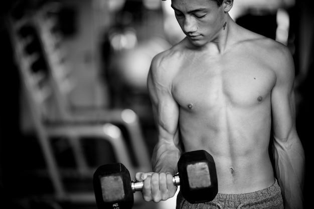 체육관에서 혼자 10대 10대 훈련 및 아령 들기 - 강하고 근육이 있는 남자 - 피트니스 및 근육 생활 방식 - 흑백 사진