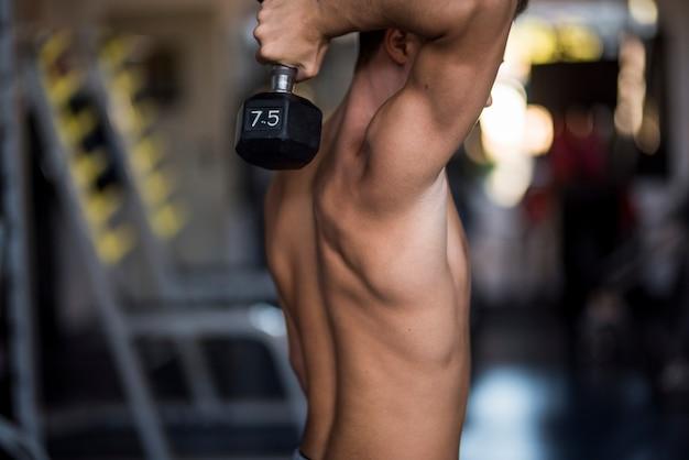 체육관에서 혼자 10대 10대 훈련 및 아령 들기 - 강하고 근육이 있는 남자 - 피트니스 및 근육 생활 방식