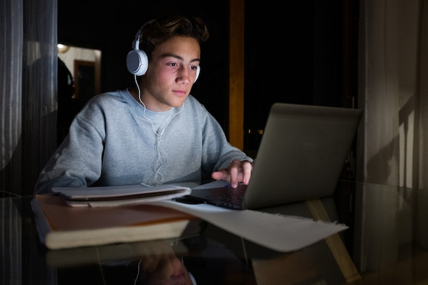 한 10대 밀레니엄 세대는 자신의 노트북을 사용하여 밤에 숙제를 하고 음악을 듣습니다 - 온라인 수업 및 수업 개념 및 생활 방식 - 집에서 pc로 작업