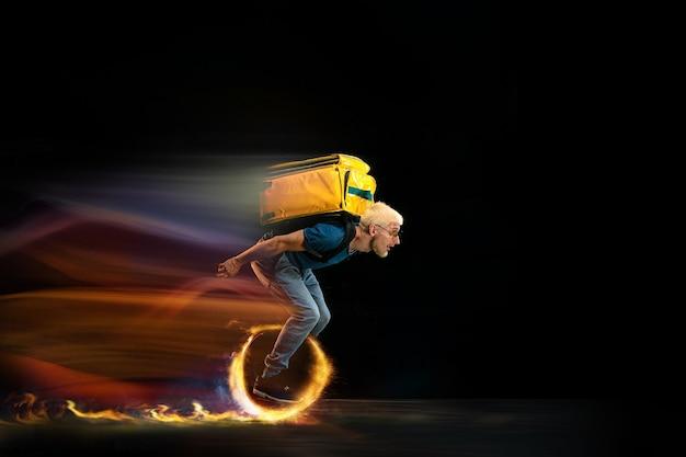 ワンゴー。速い配達サービス-暗い背景に火をつけて一輪車を運転している配達員。広告のコピースペース。検疫中の食品および商品の注文の超高速配送。