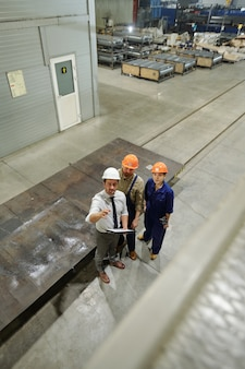 One of three young engineers in uniform and hardhats pointing at new huge industrial machine while showing it to colleagues