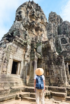 One tourist visiting angkor ruins amid jungle, angkor wat temple complex, travel destination cambodia. woman with traditional hat, rear view.