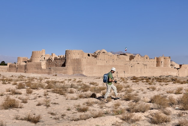 One tourist with camera walks along wall of the ancient persian fortress saryazd.