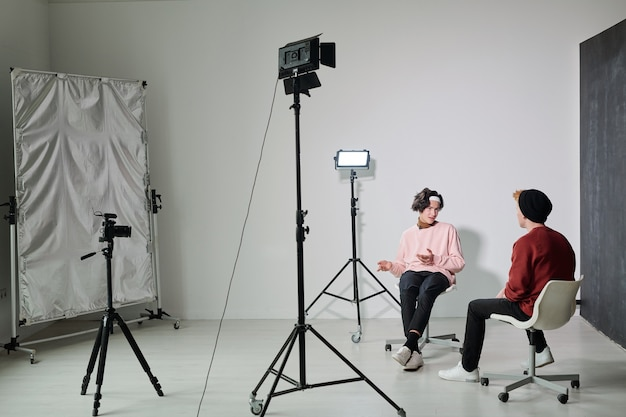 One of two young male vloggers explaining something to his friend while both sitting on chairs in front of each other in studio