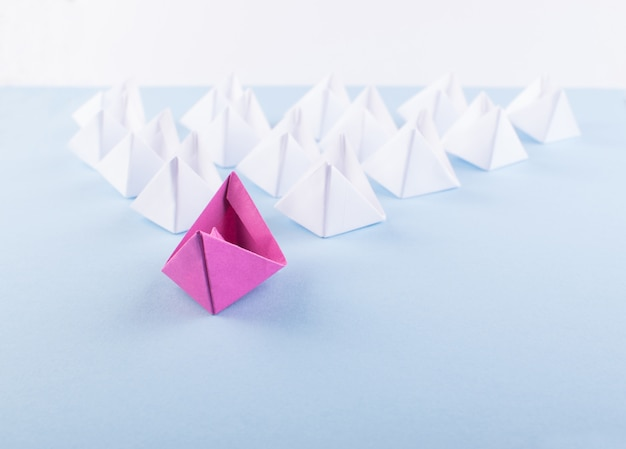 One unique pink paper boat among many ones. different paper ships as individuality and leadership concept