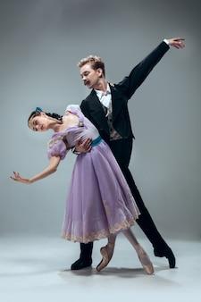 Один блок. красивые современные бальные танцоры, изолированные на серой стене. чувственные профессиональные артисты танцуют вальс, танго, медленный лис и квикстеп. гибкий и невесомый.