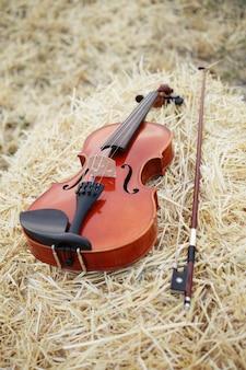 Скрипку и смычок положили на груду соломы в поле. музыкальное обучение игре на скрипке