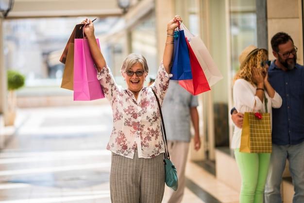 Одна красивая женщина в торговом центре, покупающая одежду и подарки - счастливый пожилой человек с руками с сумками в руке в торговом центре